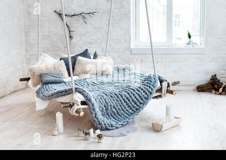 White loft interior in classic scandinavian style. Hanging bed suspended from the ceiling. Cozy large folded gray - Stock Photo