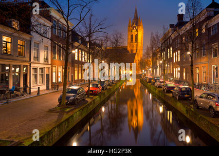 The Old Church reflected in a canal in Delft in The Netherlands at night. - Stock Photo