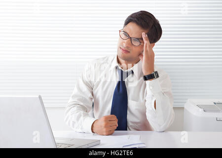 Young man looking frustrated and angry holding forehead sitting at office desk - Stock Photo