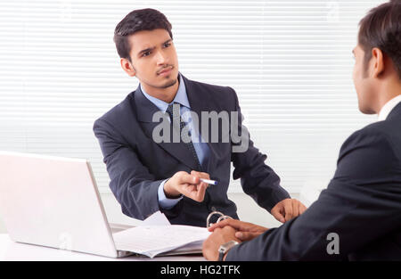 Two businessmen seriously discussing work at office - Stock Photo