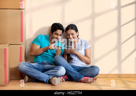 Young couple online shopping using mobile - Stock Photo