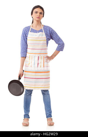 Young Indian woman holding kitchen utensil against white background - Stock Photo