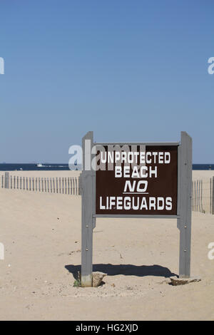 A sign reads 'Unprotected Beach No Lifeguards.' A clear blue sky is seen in the background along with a beach fence - Stock Photo