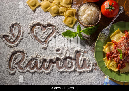 Handwriting in Flour on Wood Surface with Plate of Raviolis and Marinara - Stock Photo