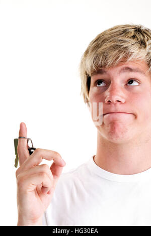 Young man holding car keys and looking upwards with a questioning look on his face - Stock Photo