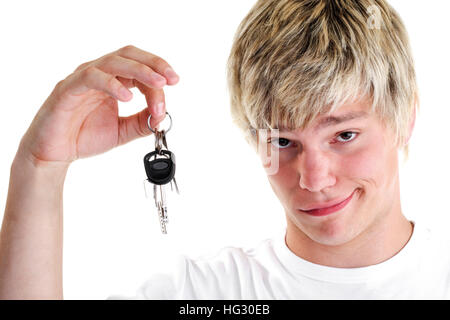 Young man holding car keys, looking skeptical - Stock Photo