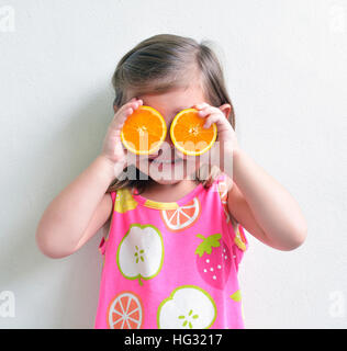 Young girl holding oranges slices over eyes - Stock Photo