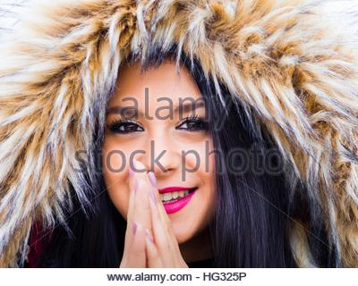 Teen girl portrait attractive cold weather outside blowing hot air into hands hoodie beautiful face smiling at camera - Stock Photo