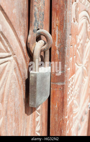 Old rusty padlock on a wooden door with carvings - Stock Photo