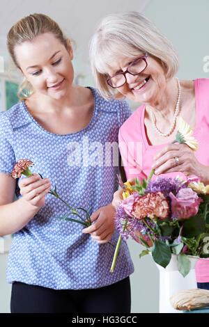 Senior Woman With Teacher In Flower Arranging Class - Stock Photo