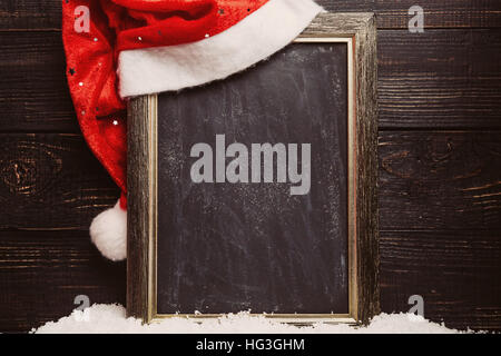 Red Santa hat on the dirty blackboard with snow. Frame with copyspace, Christmas background - Stock Photo