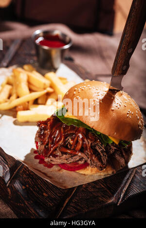 Close up of a burger being served with French fries - Stock Photo