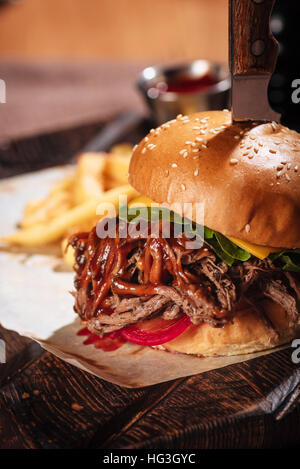 Close up of big burger being served in restaurant - Stock Photo