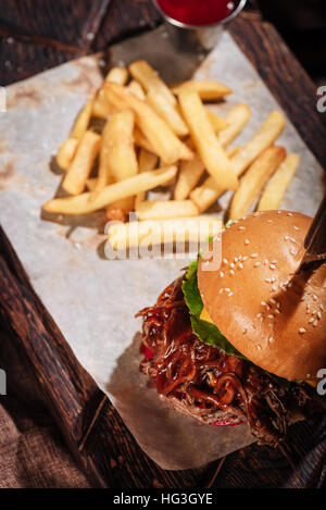 Top view of big burger being served with French fries - Stock Photo