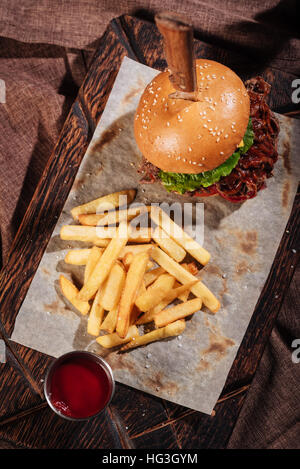 Top view of burger and French fries standing on tray - Stock Photo