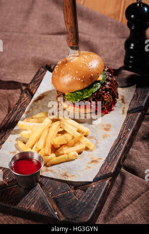 Close up of burger and French fries standing on tray - Stock Photo