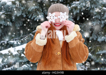 beautiful woman on winter outdoor posing with big snowflake toys, holiday concept, snowy fir trees in forest, long - Stock Photo