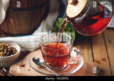Pouring hot floral tea to a glass - Stock Photo