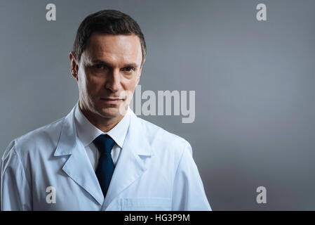 Handsome doctor standing on a grey background - Stock Photo