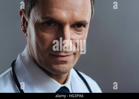 Close up of a doctor standing on grey background - Stock Photo