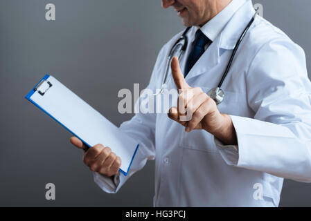 Close up of professional doctors hands holding documents - Stock Photo