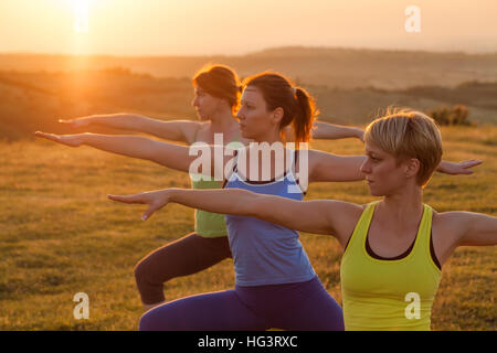 Three girls are practicing yoga in sunset. Warrior position. - Stock Photo