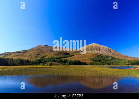 Beinn Na Caillich mountain reflected into still waters of Loch Cill Chriosd, nearby B8083 road from Broadford to - Stock Photo