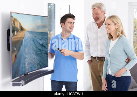 Man Demonstrating New Television To Mature Couple At Home - Stock Photo