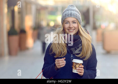 Gorgeous young woman out Christmas shopping in a knitted winter cap smiling happily as she glances behind her while - Stock Photo
