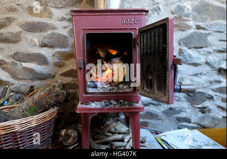 Old Jotul 602C woodburning stove with door open logs burning fire flames in a stone cottage in Wales UK  KATHY DEWITT - Stock Photo
