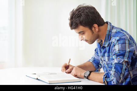 Young man studying and making notes