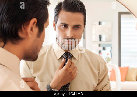 Businessman looking at self in mirror - Stock Photo