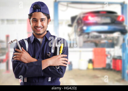 Portrait of car mechanic with hand tools in garage - Stock Photo