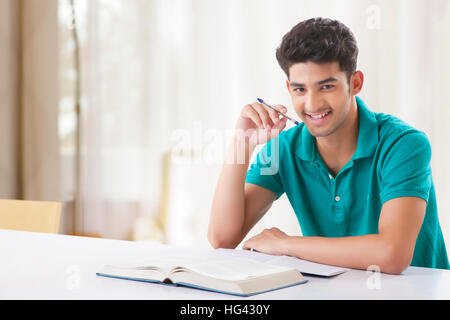 Young student is sitting on desk with open book and learns for his exams. He looks neutral into camera - Stock Photo