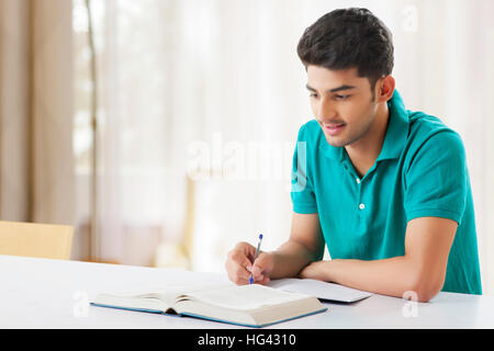 Young student is sitting on desk with open book and learns for his exams - Stock Photo