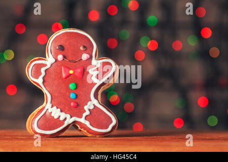 Smiling gingerbread man on Christmas bokeh background - Stock Photo