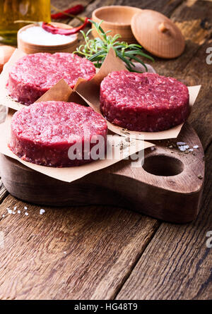 Organic raw ground beef, round patties for making homemade burger on wooden cutting board - Stock Photo