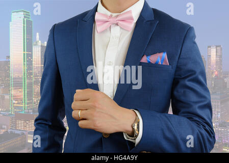 Man in blue suit with pink bow tie, flower brooch, and pink blue strip pocket square, close up - Stock Photo