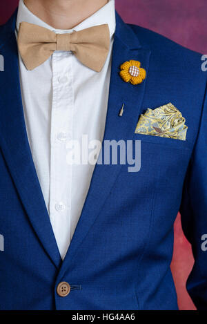 Man in blue suit with brown bow tie, flower brooch, and classic texture pocket square, close up - Stock Photo