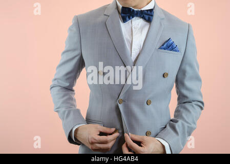Man in grey suit, plaid texture, blue bowtie and pocket square, close up white background - Stock Photo