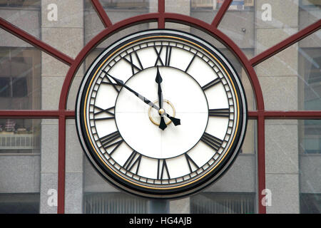 Clock with roman numerals for hours, hands at nine minutes to twelve o'clock on a glass wall, building in background - Stock Photo