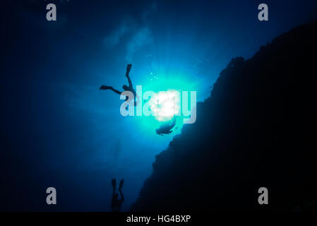 scuba divers swimming along coral reef wall.  at Yap island Micronesia. - Stock Photo
