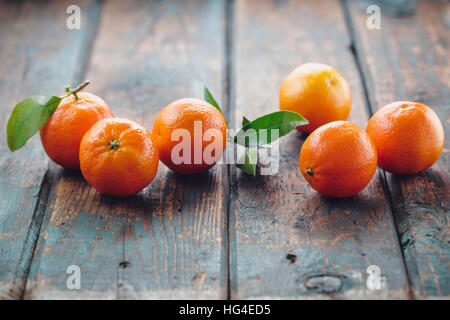 Fresh clementines with leaves on wooden table. - Stock Photo
