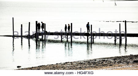 A silhouette of people walking on a jetty at Rhos on Sea, Colwyn Bay in North Wales, UK. - Stock Photo