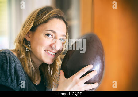 unwrapped easter egg woman happy smile portrait - Stock Photo
