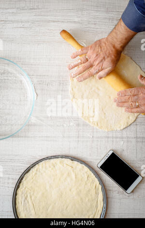 Man cooking dough for two pizzas on the kitchen vertical - Stock Photo