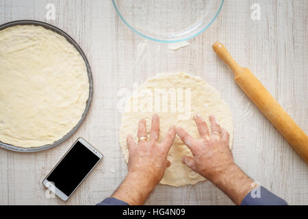 Man cooking dough for two pizzas on the wooden table horizontal - Stock Photo