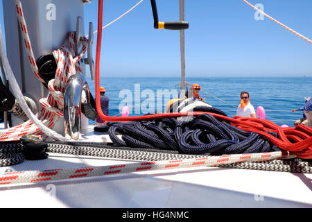 Rigging on the deck of a luxury yacht with day trippers on the foredeck - Stock Photo