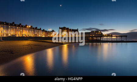 Aberystwyth promenade buildings and Pier in early evening. A crescent moon and the planet  Venus also pictured. - Stock Photo
