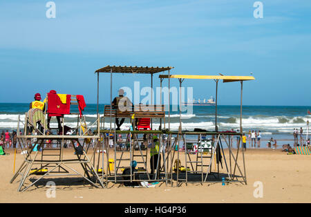Lifeguards on viewing platform watch over many unknown people on beach against ocean and blue skyline - Stock Photo